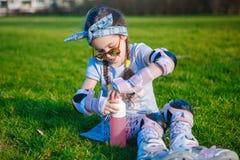 Ragazza sveglia senza dente di latte e treccia due che si siede sull'erba nei pattini di rullo ed occhiali da sole e bottiglia ap fotografia stock