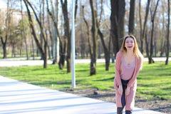 Ragazza sveglia sorridente che esamina macchina fotografica e che cammina nel parco di primavera Fotografia Stock