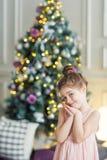 Ragazza sveglia sui precedenti dell'albero di Natale ritratto di un bambino nell'interno del nuovo anno fotografie stock libere da diritti