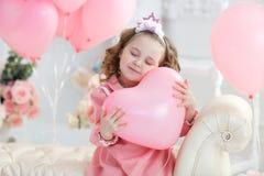 Ragazza sveglia sul pavimento bianco in studio con un mazzo di palloni rosa immagine stock libera da diritti