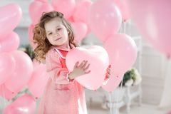 Ragazza sveglia sul pavimento bianco in studio con un mazzo di palloni rosa fotografia stock libera da diritti