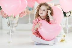 Ragazza sveglia sul pavimento bianco in studio con un mazzo di palloni rosa immagini stock libere da diritti