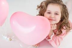 Ragazza sveglia sul pavimento bianco in studio con un mazzo di palloni rosa fotografia stock