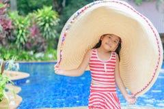 Ragazza sveglia in un costume da bagno ed in un grande cappello fotografia stock libera da diritti