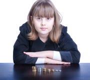 Ragazza sveglia in un uniforme scolastico che si siede ad una tavola ed alle monete di conteggi Fotografia Stock Libera da Diritti