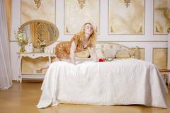 Ragazza sveglia in vestito dallo zecchino dell'oro che riposa su un letto bianco in una stanza con lo stucco sulle pareti fotografie stock
