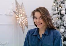 Ragazza sveglia vicino all'albero di Natale che porta camicia blu che esamina macchina fotografica e sorriso Immagine Stock