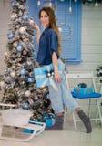Ragazza sveglia vicino all'albero di Natale con un regalo in sue mani Fotografia Stock