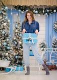 Ragazza sveglia vicino all'albero di Natale con un regalo in sue mani Immagine Stock Libera da Diritti