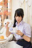 Ragazza tailandese asiatica sveglia della High School in uniforme che prepara il suo tè Fotografie Stock Libere da Diritti