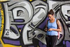 Ragazza tatuata nell'appoggiarsi la parete dei graffiti Immagine Stock Libera da Diritti