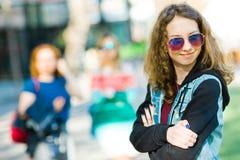 Ragazza Teenaged che aspetta nella città fotografia stock