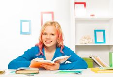 Ragazza teenager astuta con i libri ed i manuali sulla tavola Fotografie Stock