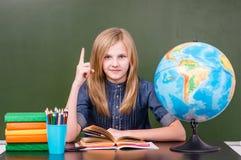 Ragazza teenager in aula vicino alla lavagna verde vuota che mostra dito su Fotografia Stock