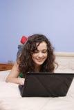 Ragazza teenager in base che osserva sul suo computer portatile Immagine Stock Libera da Diritti