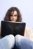 Ragazza teenager in base che osserva sul suo computer portatile Immagini Stock Libere da Diritti