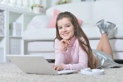 Ragazza teenager bella che per mezzo del computer portatile Fotografia Stock Libera da Diritti