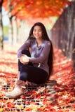 Ragazza teenager biraziale che si siede sotto gli alberi di acero variopinti in autunno Immagine Stock