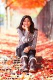 Ragazza teenager biraziale che si siede sotto gli alberi di acero variopinti in autunno Fotografie Stock Libere da Diritti