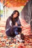 Ragazza teenager biraziale che si siede sotto gli alberi di acero variopinti in autunno Fotografia Stock