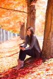 Ragazza teenager biraziale che si siede sotto gli alberi di acero variopinti in autunno Fotografia Stock Libera da Diritti
