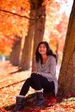 Ragazza teenager biraziale che si siede sotto gli alberi di acero variopinti in autunno Immagini Stock