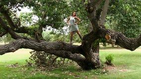 Ragazza teenager caucasica attraente che sta sui rami di albero video d archivio
