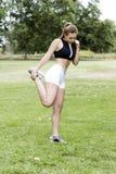 Ragazza teenager caucasica che allunga gamba in parco Fotografia Stock Libera da Diritti