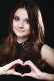 Ragazza teenager che fa simbolo di amore di forma del cuore con le mani Immagini Stock
