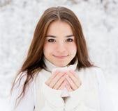 Ragazza teenager che gode di grande tazza della bevanda calda durante il giorno freddo Fotografia Stock