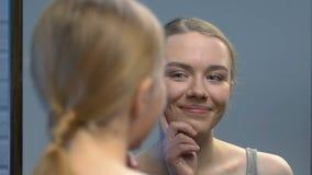 Ragazza teenager che guarda in specchio e che gode della sua bellezza, preparante per la prima data video d archivio