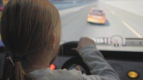 Ragazza teenager che guida la galleria dell'automobile in macchina del gioco ad un parco di divertimenti video d archivio