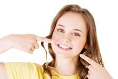 Ragazza teenager che indica sui suoi denti perfetti fotografia stock