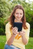 Ragazza teenager che legge libro elettronico Fotografia Stock