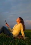 Ragazza teenager che legge libro elettronico all'aperto Immagini Stock