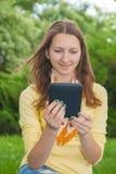 Ragazza teenager che legge libro elettronico Fotografie Stock