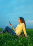 Ragazza teenager che legge libro elettronico Immagini Stock