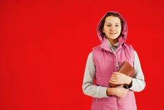 Ragazza teenager che rimane con un libro Immagini Stock Libere da Diritti