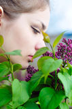 Ragazza teenager che sente l'odore dei fiori lilla Fotografia Stock Libera da Diritti