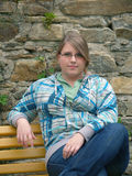Ragazza teenager che si siede sul banco Fotografie Stock Libere da Diritti