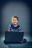 Ragazza teenager che si siede sul pavimento che gioca computer portatile Fotografie Stock Libere da Diritti