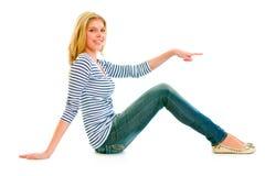Ragazza teenager che si siede sul pavimento e che indica barretta Fotografia Stock
