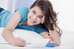 Ragazza teenager che si trova sul pavimento che scrive una lettera o una nota Fotografie Stock Libere da Diritti