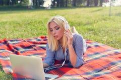 Ragazza teenager che studia con un computer portatile sul prato in parco Fotografia Stock
