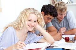 Ragazza teenager che studia nella libreria con i suoi amici Immagini Stock Libere da Diritti