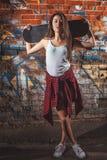 Ragazza teenager con i boardrs del pattino, stile di vita urbano Fotografia Stock Libera da Diritti