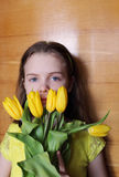 Ragazza teenager con i tulipani gialli Foto del ritratto sui precedenti di legno Fotografia Stock Libera da Diritti