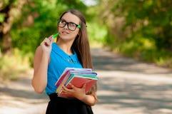 Ragazza teenager con i vetri ed i libri in mani Fotografia Stock Libera da Diritti