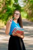 Ragazza teenager con i vetri ed i libri in mani Fotografie Stock