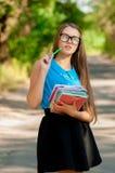 Ragazza teenager con i vetri ed i libri in mani Immagine Stock